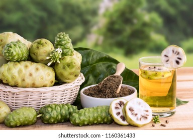 Noni fruit juice or Morinda Citrifolia with noni slice and noni powder for health on the wooden background with copy space for text.
