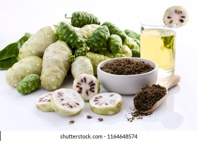 Noni fruit juice or Morinda Citrifolia with noni slice and noni powder for health on the white background with copy space for text.