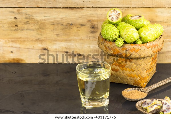 Noni fruit  and noni juice with noni powder on black table.Fruit for health and herb for health.
