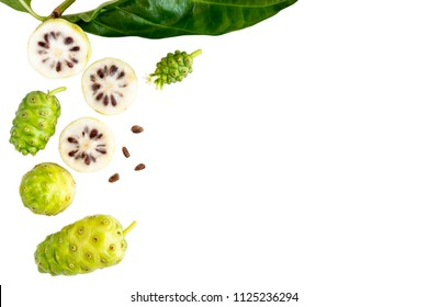 Noni fruit or Morinda Citrifolia and noni slice with seed and green leaves of the noni isolated on white blackground with copy space for text. Top view
