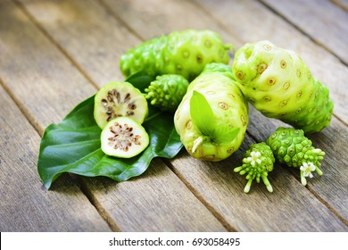 Noni fruit and Noni slice with leaf and blossom on old wooden table.