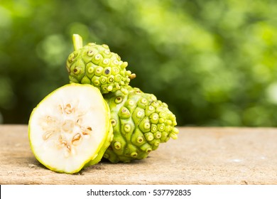 Noni fruit and noni slice on wooden table and green background.Fruit for health and herb for health.01
