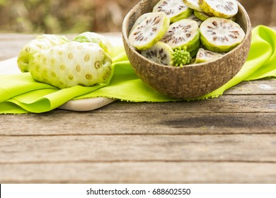 Noni fruit and noni slices in the coconut shell  on wooden table.