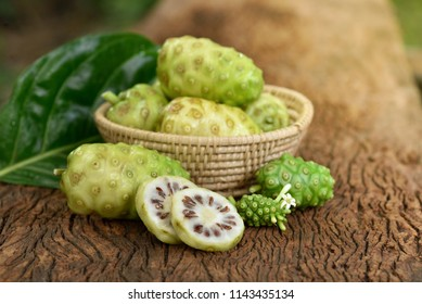 Noni or Morinda Citrifolia fruits in bamboo basket with half sliced and green leaf on old wood texture