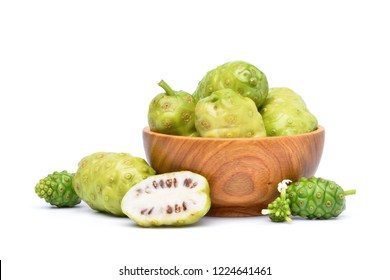 Noni or Morinda Citrifolia fruits in wooden bowl with sliced isolated on white background