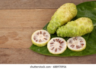 noni slice and noni fruit on green leaf wooden background.