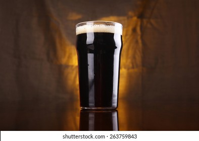 Nonic pint of dark stout beer on a table with a warm colored drapery in the background