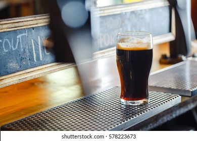 Nonic pint glass with dark stout ale standing on a pub counter near draft taps
