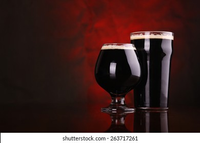 Nonic pint and snifter of dark stout beer on a wooden table over a redish background