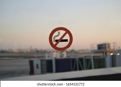 Non-smoking sign on the glass window at airport. No smoking area in air-base. Airport background.