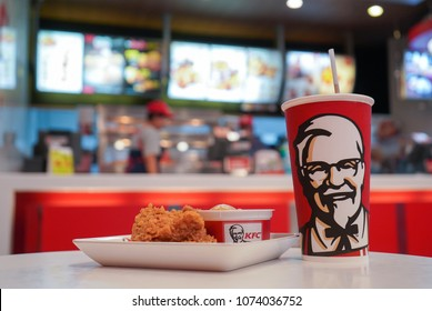 Nonthaburi, Thailand - April 22, 2018 : Cup of KFC's Cola with hot Chicken fried  and Mashed potato in the background of KFC (Kentucky Fried Chicken)restaurant.