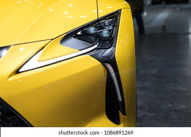 Nonthaburi , Thailand - April 7, 2018 : Lexus LC 500 yellow color hybrid car . special edition production design . luxury automobile in show room . front side view car bonnet with headlights .