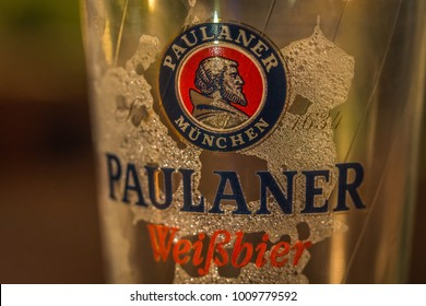 NONTHABURI, THAILAND - DEC 18, 2017: Paulaner Beer Logo on Empty Beer Glass with Beer Foam Macro Closeup Selective Focus against Dark Night After Party Relaxing Hang Out at Bar Night Soiree Background