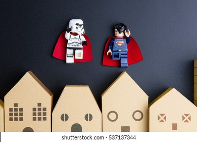 Nonthaburi, Thailand - December, 15, 2016 : Lego Super Man and Lego star wars stormtrooper are flying in the sky over home architectural model on black background.