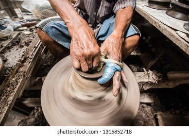 Nonthaburi, Thailand - February, 16, 2019 : Hand of potter man traditional pottery making shaping a bowl on the spinning by clay at Koh Kret Nonthaburi, Thailand.