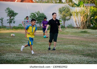 NONTHABURI, THAILAND - FEBRUARY 17 : Asian thai father training and playing football or soccer with son at playground on yard in public garden park on February 17, 2017 in Nonthaburi, Thailand.