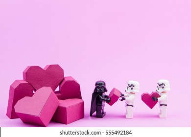 Nonthaburi, Thailand - January, 11, 2017 : Lego stormtrooper give paper box red heart shape to lego darth vader on pink background with copy space for your text.Concept Valentine's Day