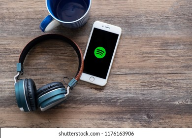 Nonthaburi, Thailand - June 17, 2018: Flat lay of headphone, a blue mug and smart phone that showing Spotify app icon on screen on wooden table. Spotify is one of popular digital music platform.