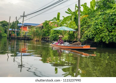 Nonthaburi, Thailand - March 31, 2018 : Old woman sells food from her boat in the canals of Nonthaburi.