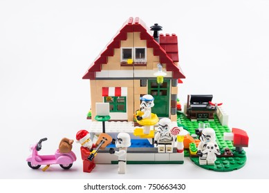Nonthaburi, Thailand - November, 07, 2017 : Lego Santa Claus giving gifts to Lego star wars stormtrooper at front of the house in Christmas day.Theme Christmas day background.