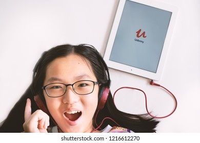 Nonthaburi, Thailand - Oct 14, 2018: High angle view of headshot of a girl with eyeglasses and red headphone connected to a tablet with Udemy app icon on screen. Udemy is online training platform.