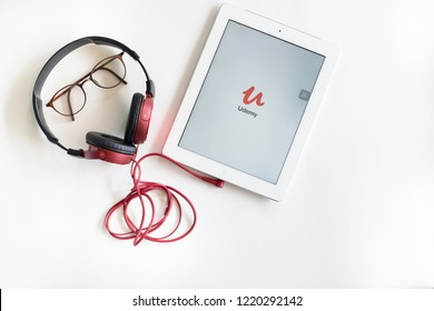 Nonthaburi, Thailand - Oct 14, 2018: Flat lay of eyeglasses, red headphone connected with a tablet showing Udemy app icon on screen. All objects isolated on white. Udemy is an online course platform.