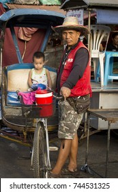NONTHABURI (THAILAND) - OCTOBER 2017: Rickshaw driver with little kid at the market  in  Nonthaburi