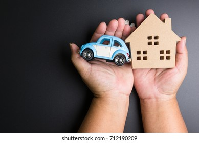 Nonthaburi, Thailand - September, 08, 2017 : Volkswagen Toy car and wooden house in man hands on a black background.Business concept.Real estate concept Nonthaburi, Thailand
