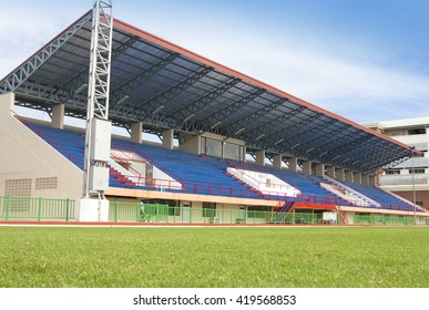 NONTHABURI, THAILAND - SEPTEMBER 27 : Red treadmill, Red running track at the stadium with green grass on blue sky. September 27, 2013 in Nonthaburi, Thailand