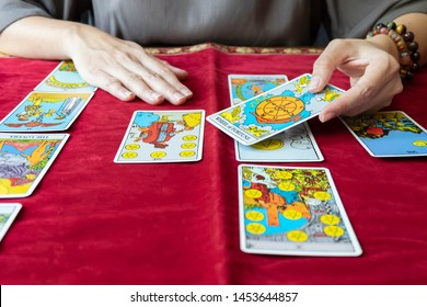 Nonthaburi,Thailand - July 16 2019 : Tarot reader reading tarot cards face up on red tablecloth.Tarot reader hand holding WHEEL of FORTUNE tarot cards.Fortune teller reading  and  forecasting concept