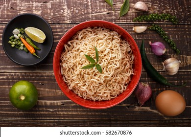 noodle in bowl and ingredients on wood background top view
