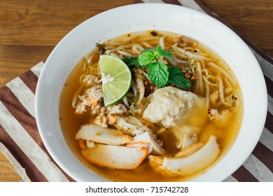 Noodle pork soup with Tom Yam spicy in white bowl on wooden table background.