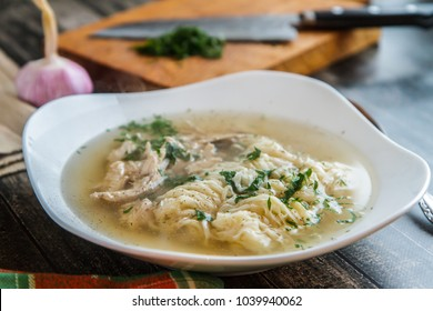Noodle soup with herbs in a white plate. Russian kitchen horizontal