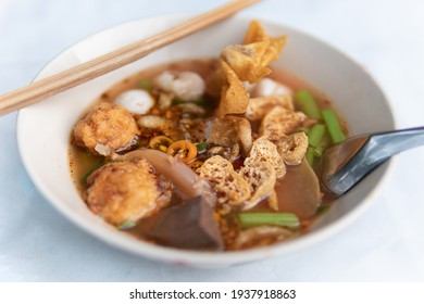 Noodle tom yum soup with fish ball, shrimp ball and fried dumplings in white bowl. Selective focus