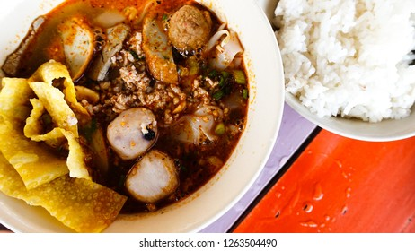 Noodle TomYum flavor and rice in a bowl on the colorful wooden table