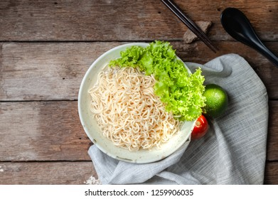 Noodles in bowl on wooden background.