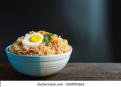 Noodles in bowl on wooden board.