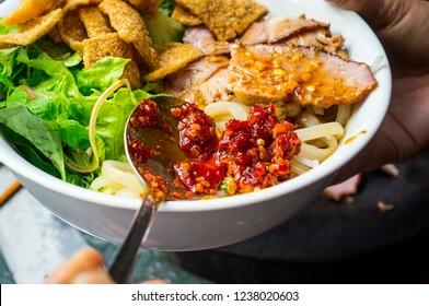 Noodles (Cao Lau Viet Nam) with chili powder, crispy cornflakes, sprouts, pork and vegetables