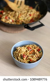 Noodles with chicken and various vegetables, prepared in wok. Served on wooden table. Selective focus.