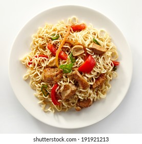 noodles with chicken and vegetables on white plate isolated on white