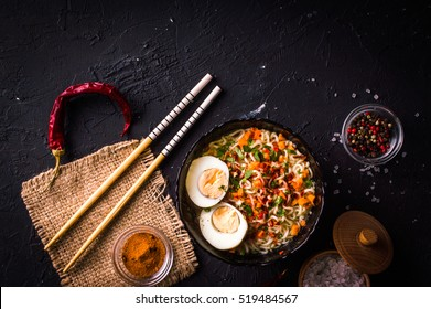 Noodles with egg and spices on a dark background