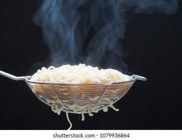 Noodles just blanched from the hot water boiler on a colander. Focus on soft steam