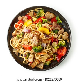 Noodles with meat and vegetables isolated on white background, top view