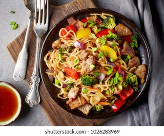Noodles with meat and vegetables on grey table, top view