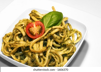 Noodles with pesto on white porcelain
