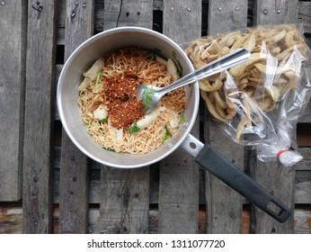 Noodles and pork fried on old wooden floors