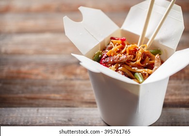 Noodles with pork and vegetables in take-out box on wooden table