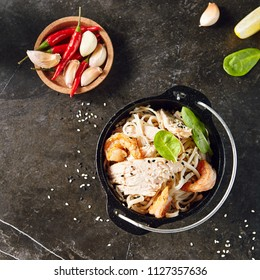 Noodles with Shrimps, Chicken, in Metal Bowler with Sesame Seeds on Natural Dark Stone Background. Meat Dish with Greens, Lettuce and Spices in Oriental Restaurant