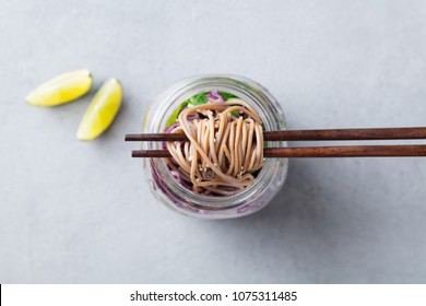 Noodles soba salad, soup with vegetables, tofu and chicken in jars. Top view. Copy space. Grey background.