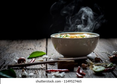 Noodles with steam and smoke in bowl on wooden background, selective focus. Asian meal on a table, junk food concept